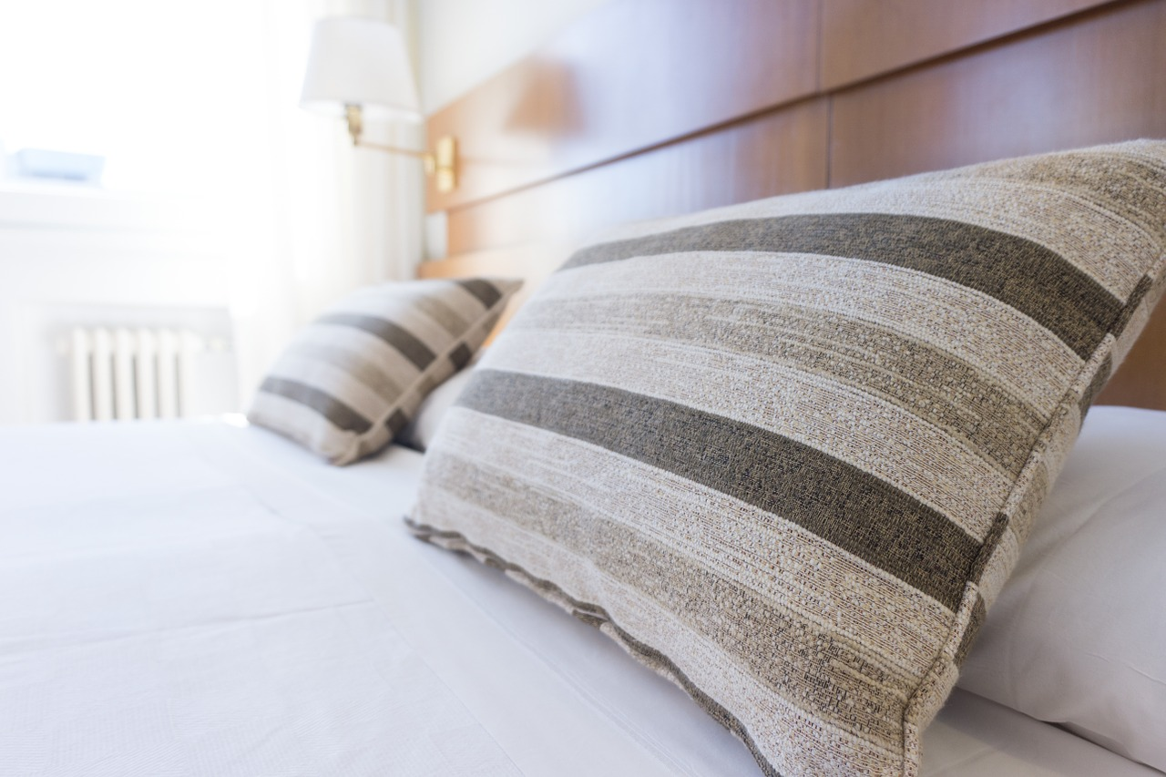 Beige striped pillows on perfectly made bed