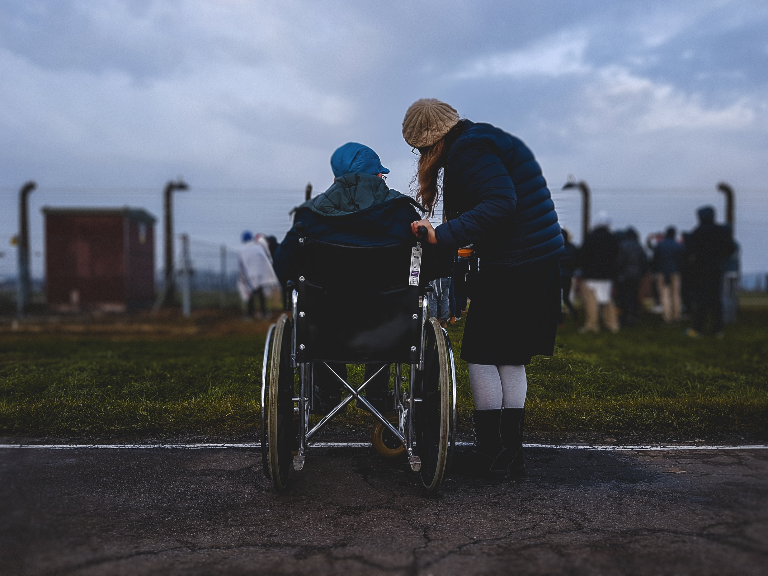 Child caring for elderly parent outdoors