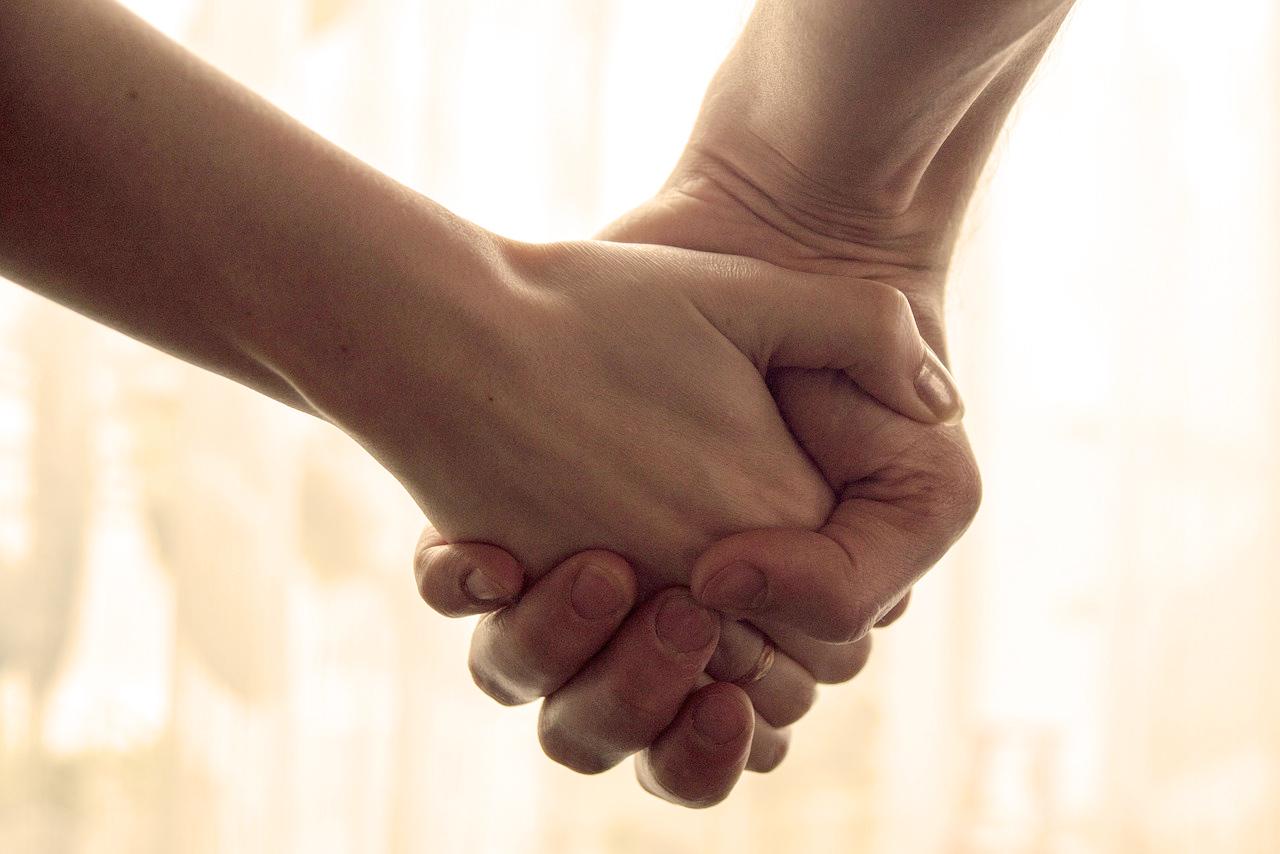 Child holding elderly parent's hand
