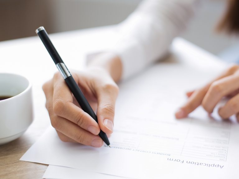 Woman completing an application for a resume for care giving job