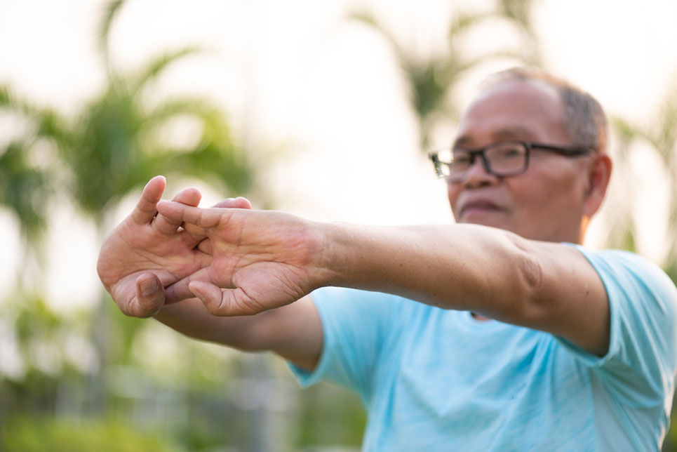 A happy old man stretching arm before outdoor exercise in a park during sunrise or sunset . Senior healthcare concept.