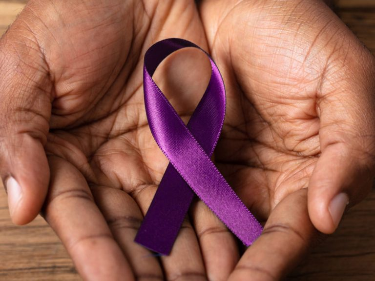 Close-up Of A Person's Hand Holding Ribbon To Support Alzheimer's Disease Awareness
