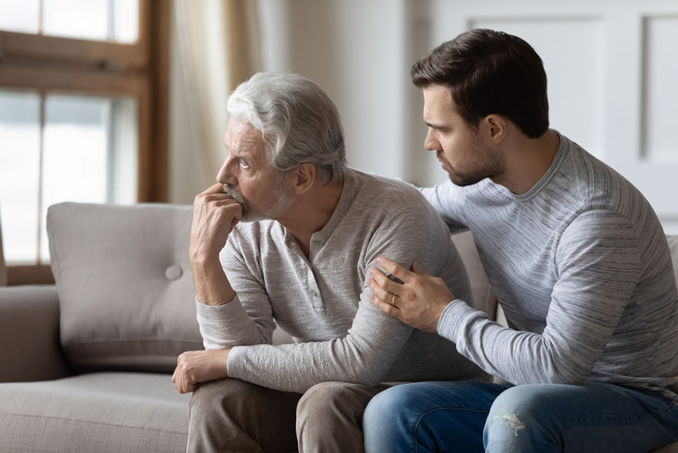 Loving young man embrace comfort upset elderly gray-haired dad suffering from depression or problems, caring adult grown-up son hug caress support mature father feeling lonely distressed at home